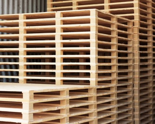 Lots of pallets stacked and ready for use. These are newly manufactured ones in open storage building.